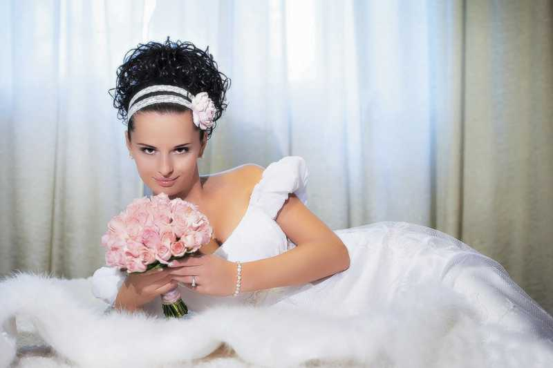 Photo Beautiful bride with bouquet of flowers on white bed.